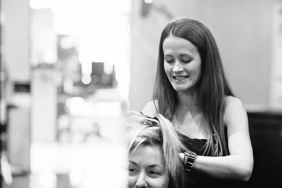 A stylist colors a client's hair in the salon. Photo by Graham Yelton.